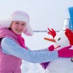 Teenage girl with snowman — Stock Photo