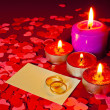 Stock Photo: Two rings and card with marriage proposal with four candles
