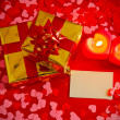 Presents and two heart shaped candles with blank card — Stock Photo
