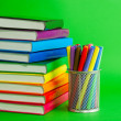 Stacks of colorful books and socket with felt pens — Stock Photo #8869472