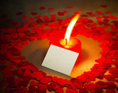 Burning heart shaped candle and a card — Stock Photo