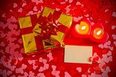 Presenteert en twee hart gevormde kaarsen met lege kaart — Stockfoto