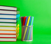 Stack of colorful books and socket with felt pens — Stock Photo