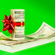 Roll of US dollars tied up with ribbon on the stack of bills — Stock Photo