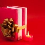 rij van boeken vastgebonden met lint en brandende kaars — Stockfoto