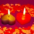 Two burning heart shaped candles - Stockfoto