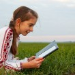 Teen girl with electronic book laying on grass — Stock Photo #9340123