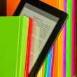 Stock Photo: Row of colorful books and electronic book reader