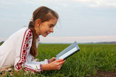 Teen girl with electronic book laying on grass — Stock Photo