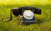 Retro styled rotary telephone on grass — Stock Photo