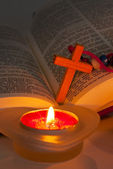 Open Bible with cross and burning candles — Stock Photo