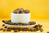 Cup full with coffee beans and chocolate candies — Stock Photo