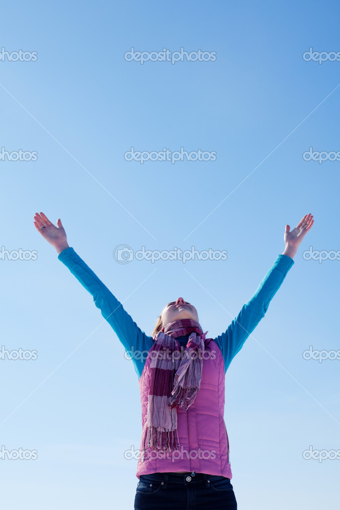 Teen girl staying with raised hands against blue sky — Stock Photo #9448332