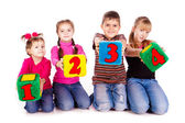 Happy kids holding blocks with numbers — Stock Photo