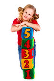 Happy girl holding blocks with numbers — Stock Photo