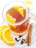 Tea with cinnamon sticks in glass cup with orange slices — Stock Photo