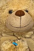 Cute sick teddy bear with a solution — Stock Photo
