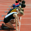 Girls on the start of the 100 meters dash — Stock Photo