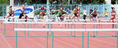 Girls on the 100 meters hurdles race — Stock Photo