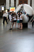 Volunteer girls gives interview in front of the the official match ball of EURO 2012 POLAND - UKRAINE, on the train station of Kiev — Stock Photo