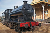 Static steam train behind the station house — Stock Photo