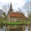 Small church by river — Stock Photo