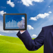 Stock Photo: Hand pointing higher graph on tablet PC