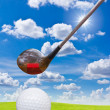 Golf ball and driver on green grass — Stock Photo