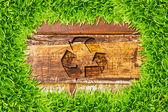 Vert herbe et réutilisez le signe sur fond de bois — Photo
