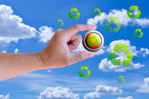 Hand holding recycle button against blue sky — Stock Photo