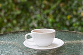 Coffee cup on glass table — Stock Photo