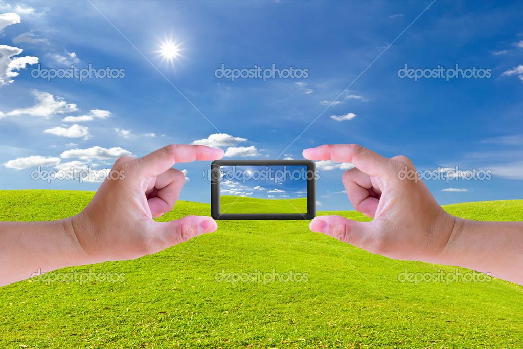 Hand holding mobile phone and green grass meadow — Stock Photo #9250455