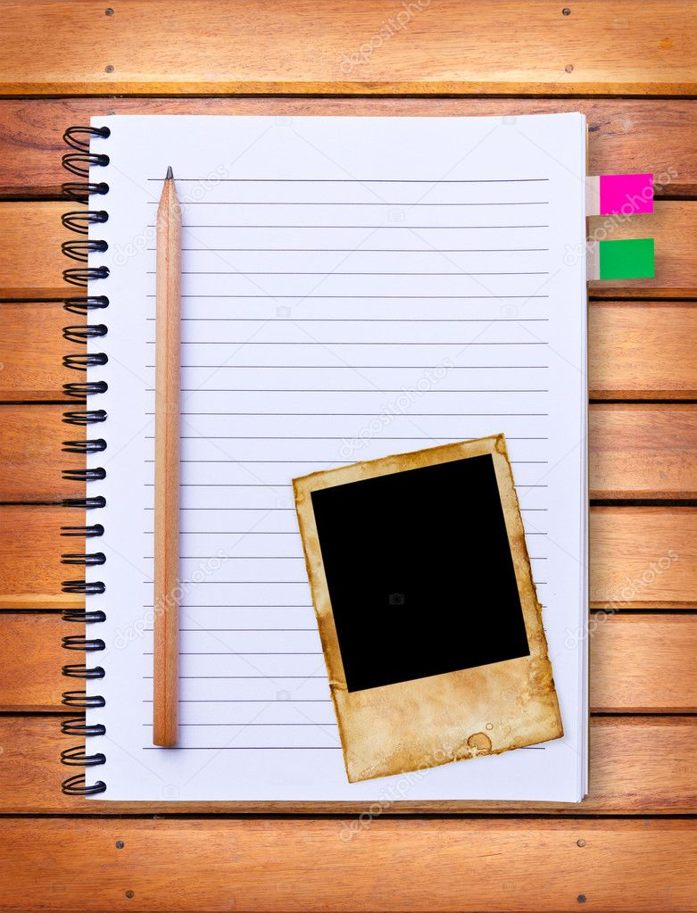 Notebook and vintage photo frame on wood background — Stock Photo #9258724