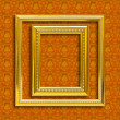 Stock Photo: Frame of golden wood on the wallpaper