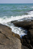 Wave of sea pass through crack of stone beach — Stock Photo