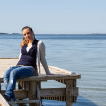 niña sentada en un muelle en la orilla del río — Foto de Stock