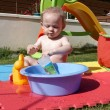 Child playing with water in garden — Stock Photo #10222706
