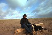 A man and his dog sitting on a log — Zdjęcie stockowe
