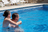 A young couple in the swimming pool — Stock Photo