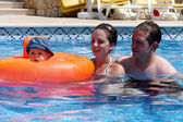 A young couple and baby in a pool — Stock Photo
