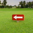 White arrow in red label on green grass at golf club — Stock Photo