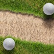 Stock Photo: Two golf ball on green grass near sand bunker