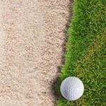 Golf ball on green grass near sand bunker — Stock Photo