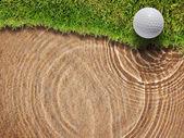 Golfball auf frisches grünes gras in der nähe von wasser bunke — Stockfoto