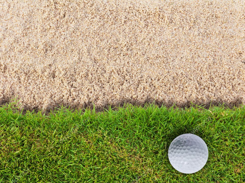 Golf ball on green grass near sand bunker — Stock Photo #9273757