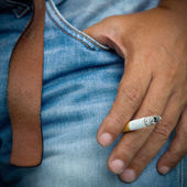 Close-up cigarette in man hand on old jean — Стоковое фото