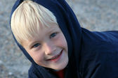 Smiling Boy Bundled up in Clothing at the Beach — Stock Photo