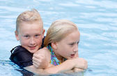 Rowdy Boy Holding Girl in Pool Water — Stock Photo