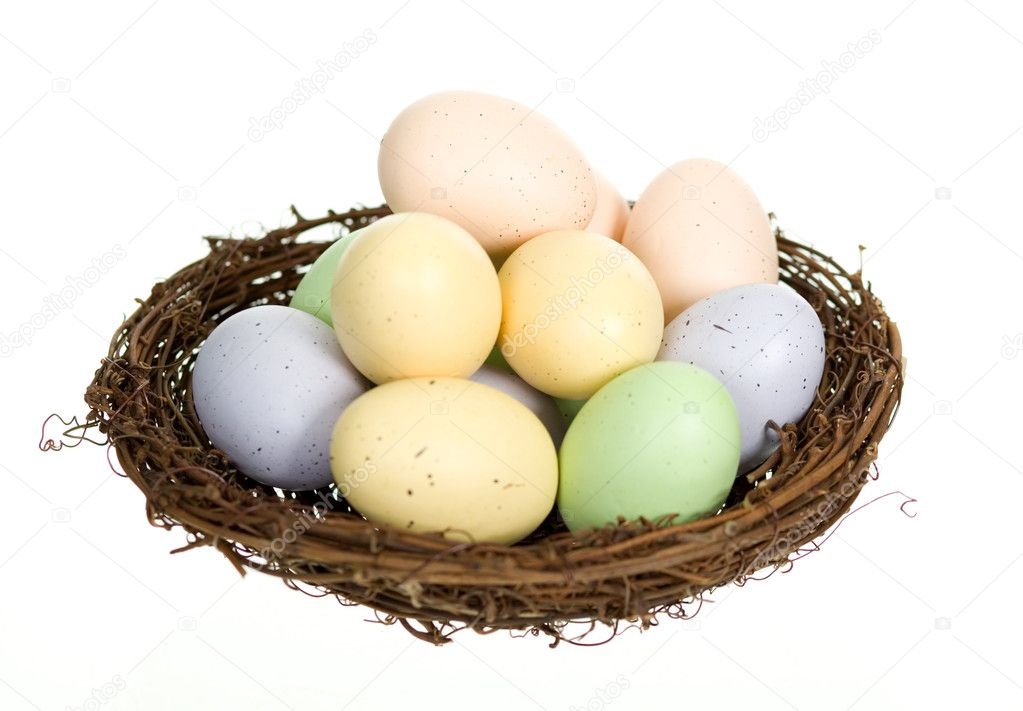 Twelve colorful speckled animal eggs in a nest, isolated on white. — Stock Photo #9660934