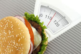 Burger on a weight scale — Stock Photo
